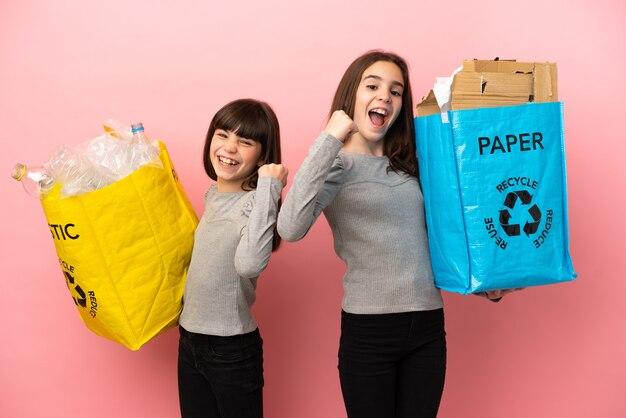 Kleine schwestern, die papier und plastik recyceln, lokalisiert auf rosa hintergrund, der einen sieg feiert