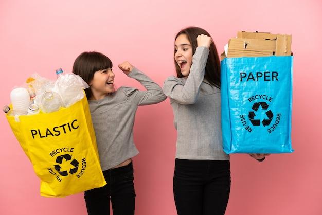 Kleine schwestern, die papier und plastik recyceln, lokalisiert auf rosa hintergrund, die einen sieg in der siegerposition feiern