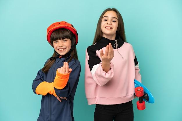 Kleine schwestern, die radfahren und skater üben, einzeln auf blauem hintergrund, die einladen, mit der hand zu kommen. schön, dass du gekommen bist