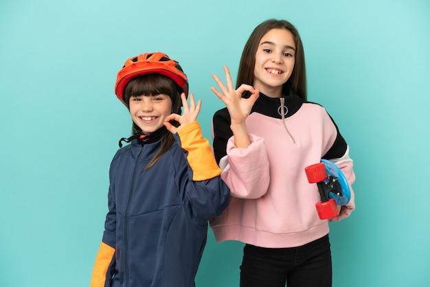 Kleine schwestern, die radfahren und skater üben, isoliert auf blauem hintergrund, die ein ok-zeichen mit den fingern zeigen