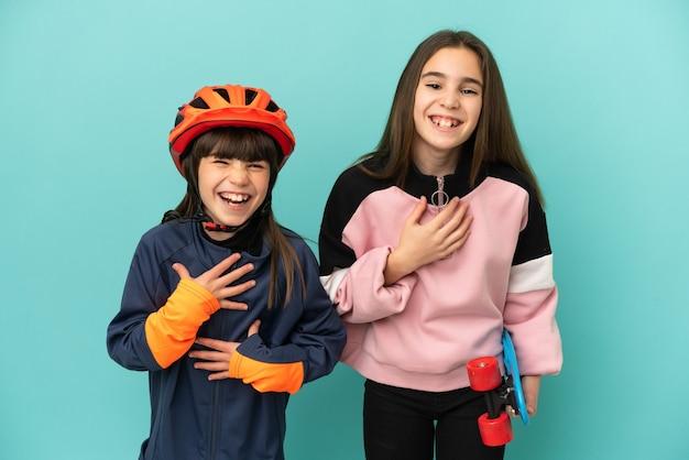 Kleine schwestern, die radfahren und skater üben, isoliert auf blauem hintergrund, lächeln viel, während sie die hände auf die brust legen