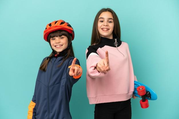 Kleine schwestern, die radfahren und skater üben, lokalisiert auf blauem hintergrund, der einen finger zeigt und hebt