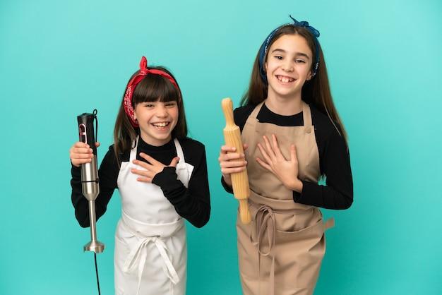 Kleine schwestern, die zu hause kochen, isoliert auf blauem hintergrund, lächeln viel, während sie die hände auf die brust legen