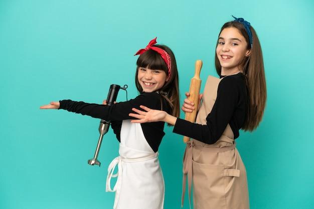 Kleine schwestern, die zu hause lokalisiert auf blauem hintergrund kochen, der zurück zeigt und ein produkt präsentiert