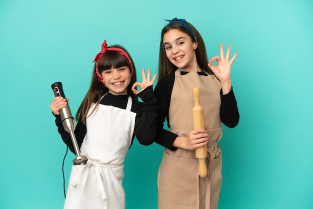 Kleine schwestern, die zu hause lokalisiert auf blauem hintergrund kochen und ein ok-zeichen mit den fingern zeigen