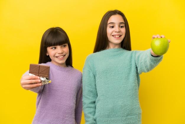 Kleine schwestern einzeln auf gelbem hintergrund, die in der einen hand eine schokoladentafel und in der anderen einen apfel nehmen taking