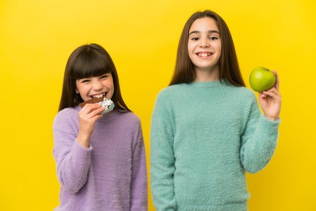 Kleine schwestern isoliert auf gelbem hintergrund, die eine schokoladentafel in der einen hand und einen apfel in der anderen nehmen