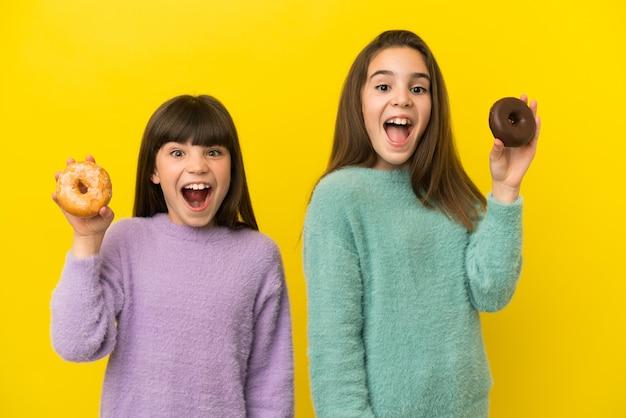 Kleine schwestern lokalisiert auf gelbem hintergrund, der donuts mit glücklichem ausdruck hält
