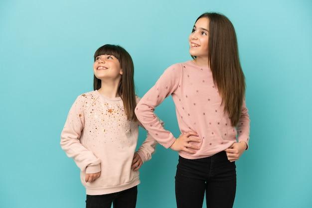 Kleine schwestern mädchen isoliert auf blauem hintergrund posieren mit armen an der hüfte und lachen laugh