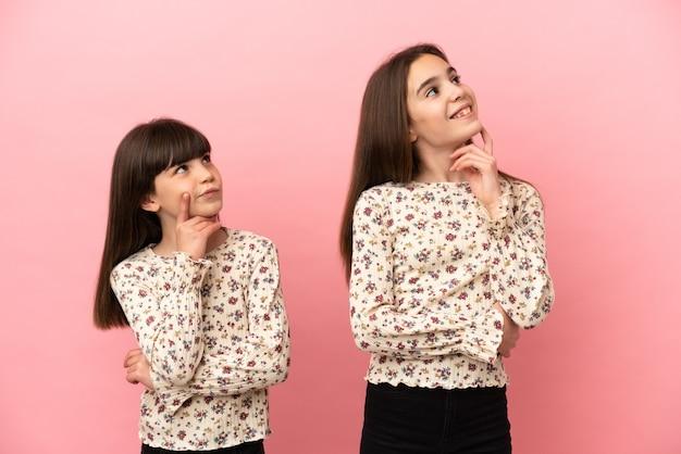 Kleine schwestern mädchen isoliert auf rosa hintergrund denken beim nachschlagen eine idee