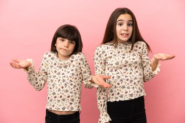 Kleine schwestern mädchen isoliert auf rosa hintergrund unglücklich und frustriert mit etwas, weil etwas nicht verstehen