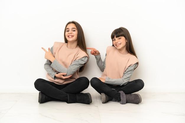 Kleine schwestern sitzen auf dem boden isoliert auf weißem hintergrund und zeigen mit dem finger zur seite in seitenlage