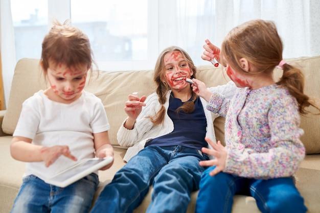 Kleine schwestern spielen mit rotem lippenstift