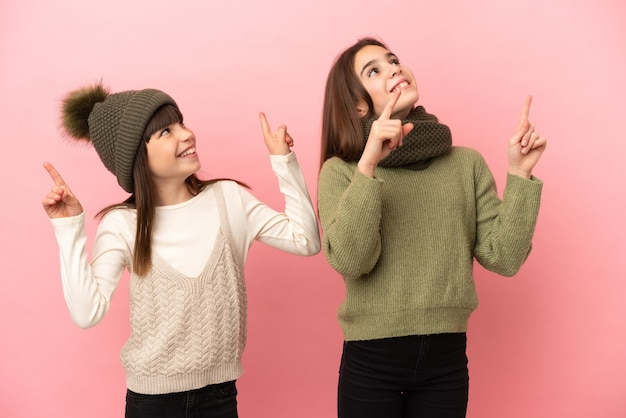 Kleine schwestern tragen eine winterkleidung einzeln auf rosa hintergrund und zeigen mit dem zeigefinger eine großartige idee
