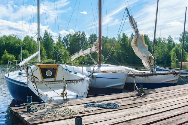 Kleine segelboote vertäut an einem holzsteg