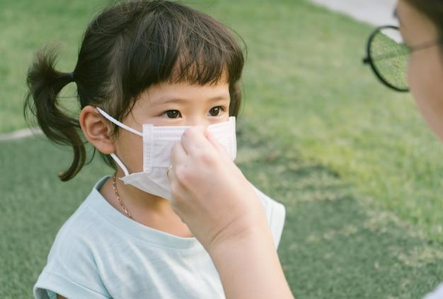 Kleine sian mädchen und mutter tragen maske zum schutz von pm2.5 und coronavirus. luftverschmutzung pm2.5 und coronavirus-konzept