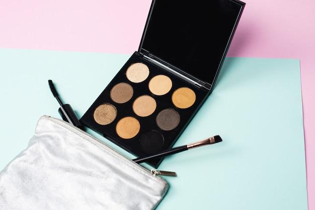 Kleine silberne kosmetiktasche mit einer großen schwarzen palette und make-up-pinseln