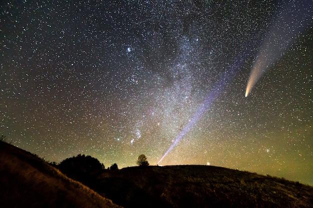 Kleine silhouette eines wissenschaftlers mit taschenlampe auf seinem kopf, der hellen lichtstrahl auf sternenhimmel zeigt