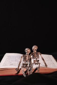 Kleine skelette auf geöffnetem buch