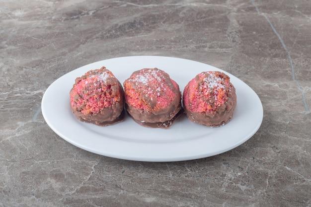 Kleine snack-kuchen auf einer platte auf marmoroberfläche