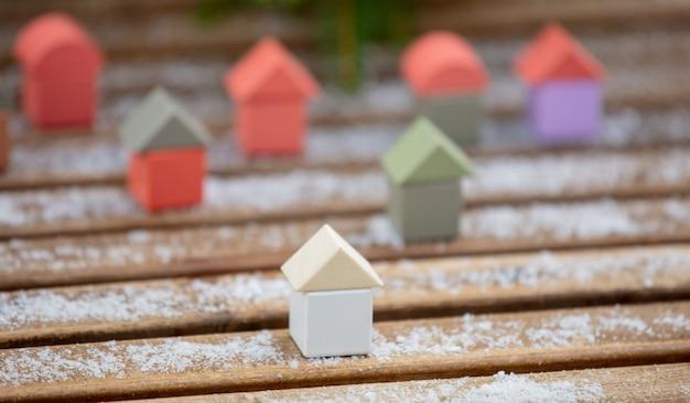 Kleine spielzeughäuser im schnee auf einem tisch