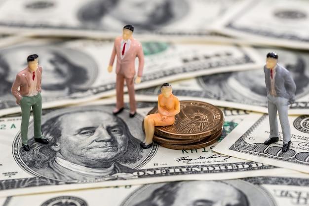 Kleine spielzeugleute auf amerikanischen münzen und banknoten