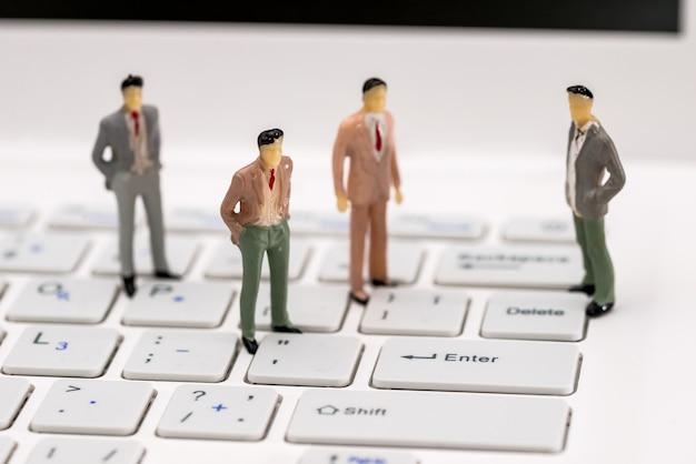 Kleine spielzeugleute sitzen auf dem laptop, ganz nah
