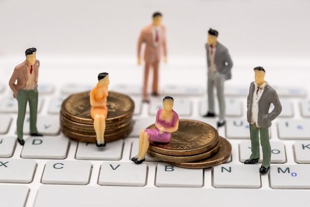 Kleine spielzeugleute stehen auf einem laptop und sitzen auf münzen