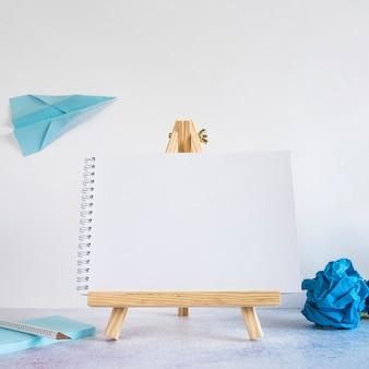 Kleine staffelei mit papierflugzeug auf schreibtisch