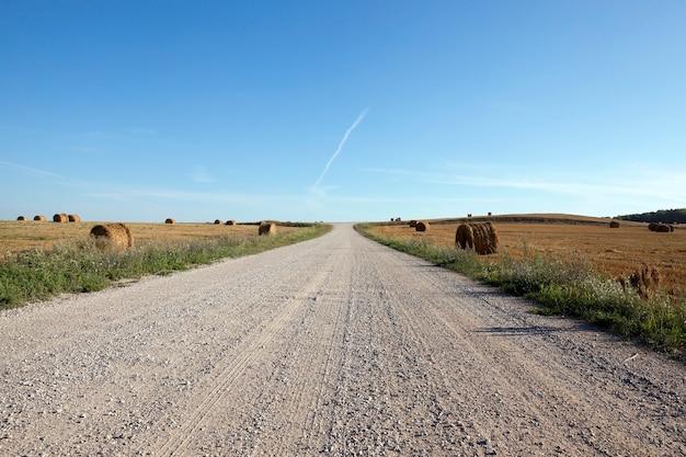 Kleine straße für autos mit schlechter straßenoberfläche, am straßenrand sind strohhaufen nach der ernte von getreide, eine landschaft mit blauem himmel bei klarem, sonnigem wetter