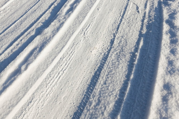 Kleine straße im winter mit spurrillen von den reifen der autos. auf dem boden liegt schnee nach schneefall.
