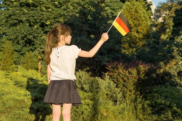 Kleine studentin, die eine flagge von deutschland hält