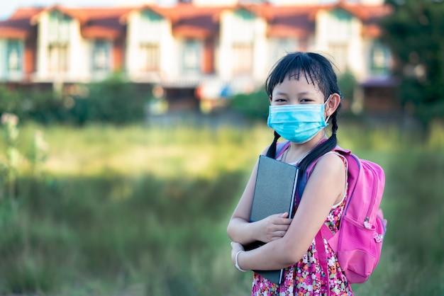 Kleine studentin, die gesichtsmaske trägt, während sie nach covid-19-quarantäne mit glück und lächeln zurück zur schule geht.