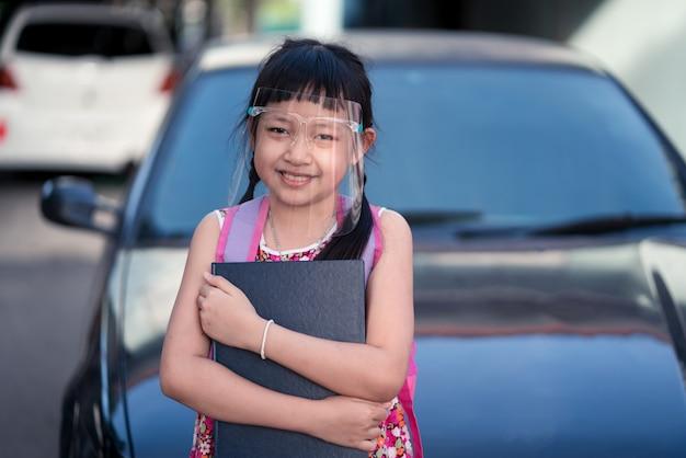 Kleine studentin, die gesichtsschutz trägt, während sie nach covid-19-quarantäne zurück zur schule geht.