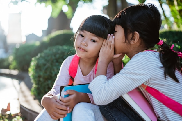 Kleine studentin flüstert ihrer freundin zu