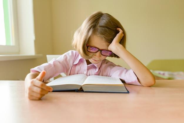 Kleine studentin sitzt an einem schreibtisch mit buch