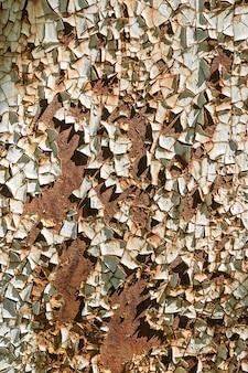 Kleine stücke abblätternder weißer farbe hängen auf dem rostigen metall das muster und die textur von rostigem eisen