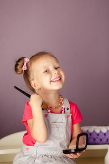 Kleine süße blondine 3-4 jahre alt sitzt mit einer reihe von kosmetika und macht make-up