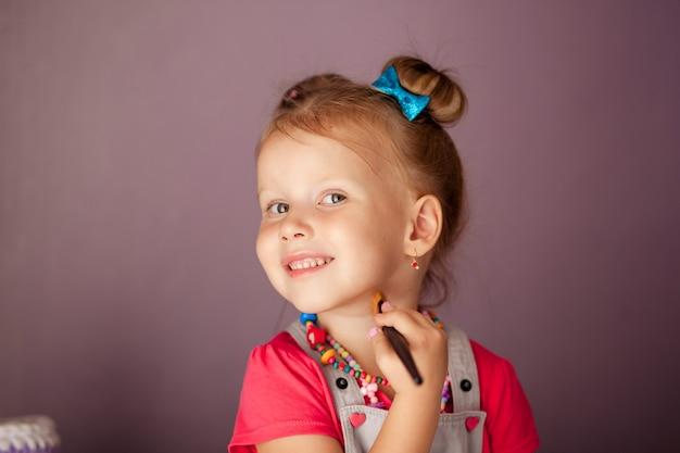 Kleine süße blondine, die vor drei jahren mit einem spiegel mit einem satz kosmetik und pinsel lächelte