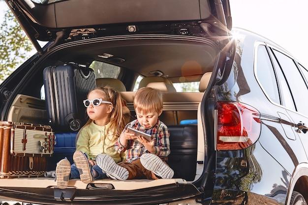 Kleine süße kinder haben spaß im kofferraum eines schwarzen autos mit kofferfamilie
