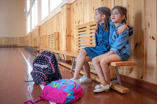 Kleine süße mädchen, grundschulmädchen, mit rucksäcken nach der schule in einer leeren schulturnhalle.