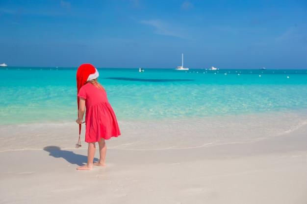 Kleine süße mädchen in roten nikolausmütze am strand