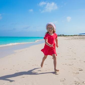 Kleine süße mädchen in roten nikolausmütze viel spaß am strand