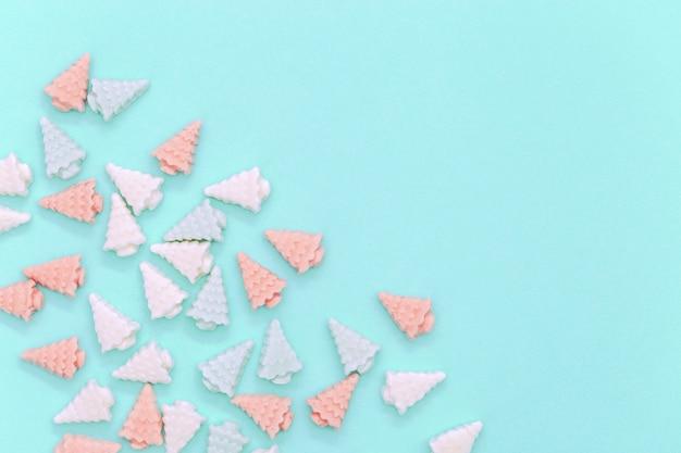 Kleine süße marshmallows in form von weihnachtsbäumen. farbige süßigkeit kreativen hintergrund für neujahr. pastellfarben