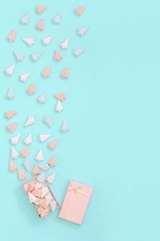 Kleine süße pralinen in form von weihnachtsbäumen sind aus der rosa geschenkbox verstreut.