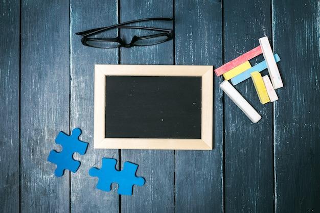 Kleine tafel, puzzleteile, gläser und bunte kreiden