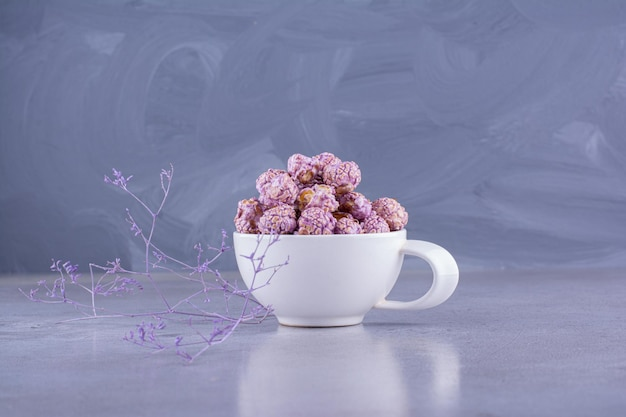 Kleine tasse popcorn-süßigkeiten auf marmorhintergrund. foto in hoher qualität
