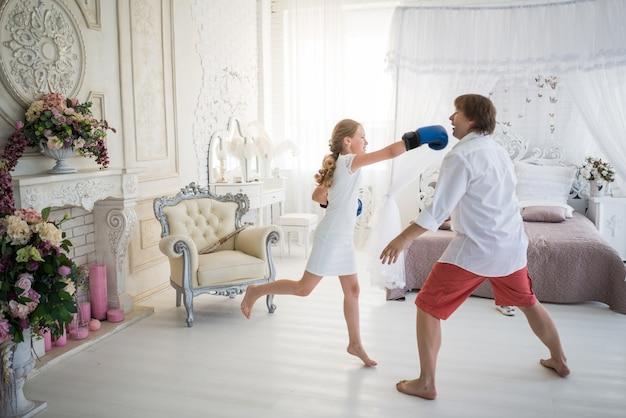 Kleine teenager-mädchen kämpft mit ihrem vater mit boxhandschuhen, während sie in einem schicken wohnzimmer mit schönem dekor stehen. konzept schädliche teenager kinder eltern-kind-beziehungsprobleme