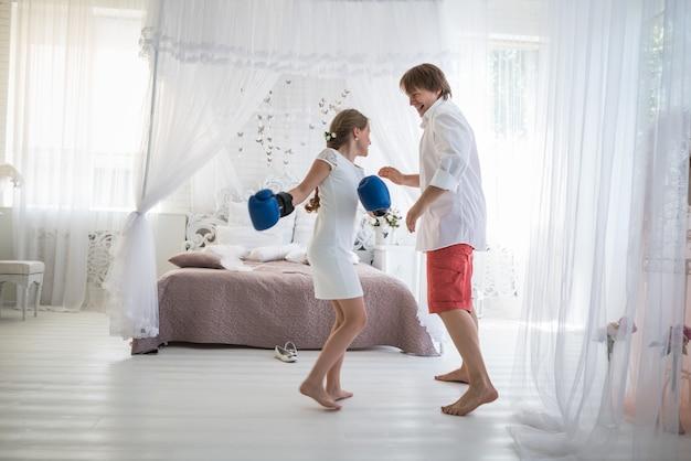 Kleine teenager-mädchen kämpft mit ihrem vater mit boxhandschuhen, während sie in einem schicken wohnzimmer mit schönem dekor stehen