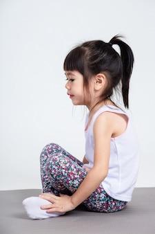 Kleine tochter, die auf yogaauflage für übung sitzt